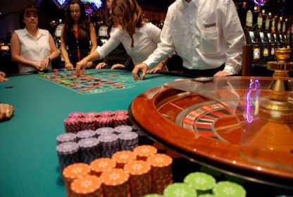 Four people stand around a roulette table