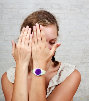A girl hides her face behind her hands