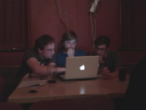The men sit behind an Apple laptop discussing something