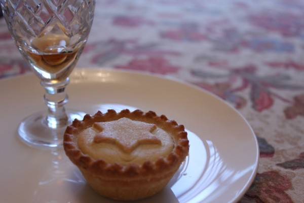 A mince pie and glass of sherry sitting on a white ceramic plate, on a cream and red-flower patterned tablecloth.